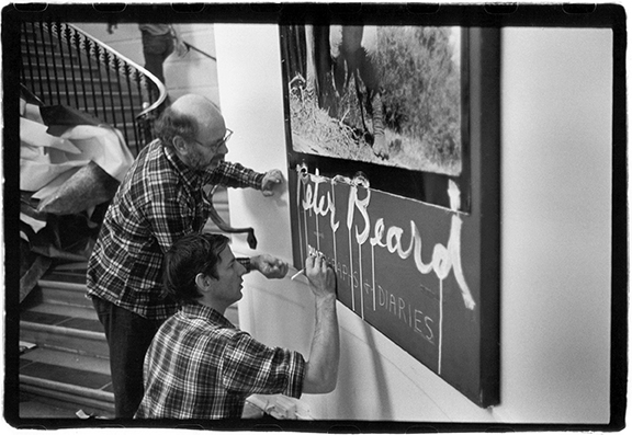 Installation designer Marvin Israel (left) and Peter Beard in the lobby of the International Center of Photography preparing for the exhibit The End of the Game