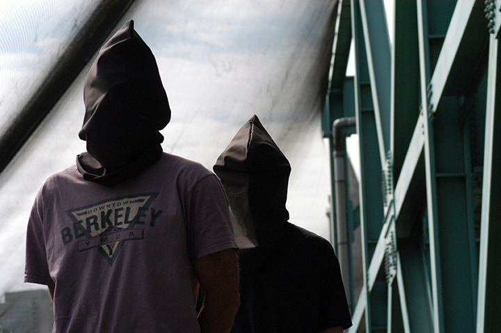 "Two hooded activists demonstrate on the morning of the first day of the 2004 Democratic National Convention (DNC) in Boston, MA against the so-called ""Free Speech Zone,"" re-dubbed by activists as the ""protest pit."""