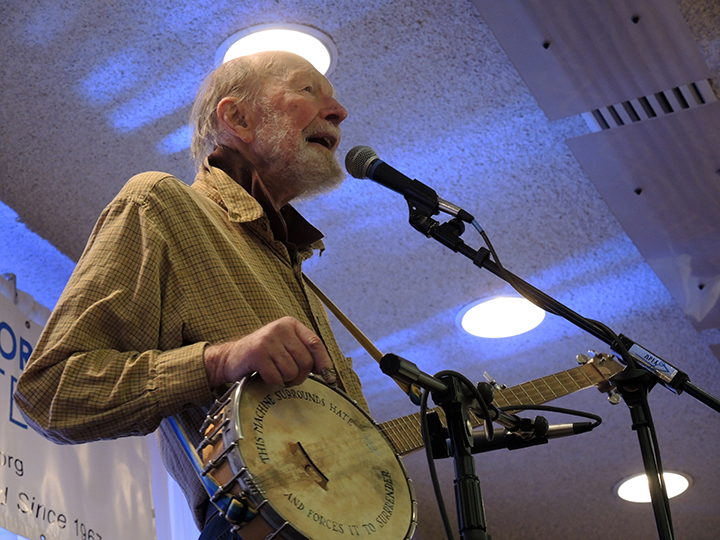 Peter Seeger sings and his banjo states: THIS MACHINE SURROUNDS HATE AND FORCES IT TO SURRENDER