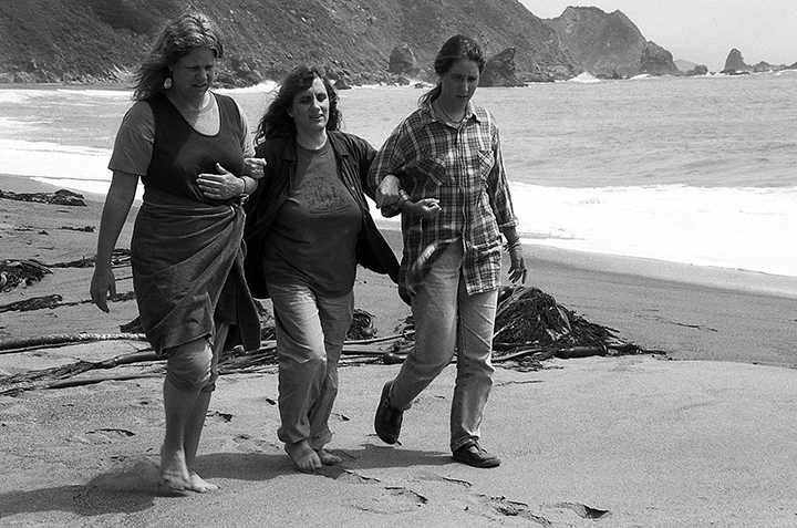 Judi Bari, center, walks on a California beach in California two years after a pipe bomb exploded under the seat of her car in May 1990.