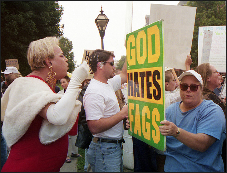 Drag queen blows bubbles at members of the Westboro Baptist Church. One of the members use the sign for bubble defense. Photo: Langelle