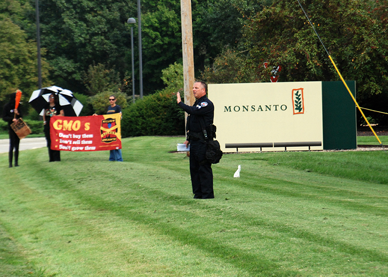 Policeman waves away some of the hundreds of demonstrators who descended on the entrance to Monsanto's world headquarters in the United States near St. Louis, MO. Photo: Orin Langelle, Creve Coeur, MO (2012) GJEP/PhotoLangelle.org